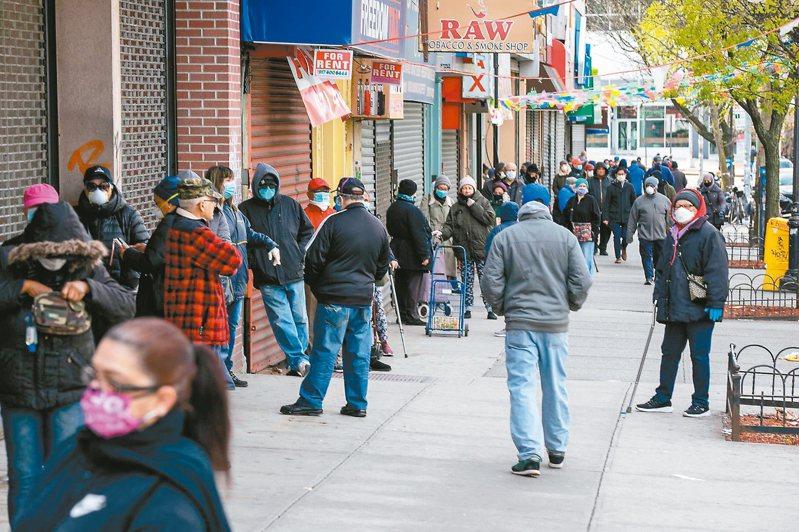 美國許多銀行因新冠病毒疫情縮短服務時間,紐約市布朗克斯區南部大道一間銀行十四日開放櫃員服務,門口大排長龍。 (法新社)