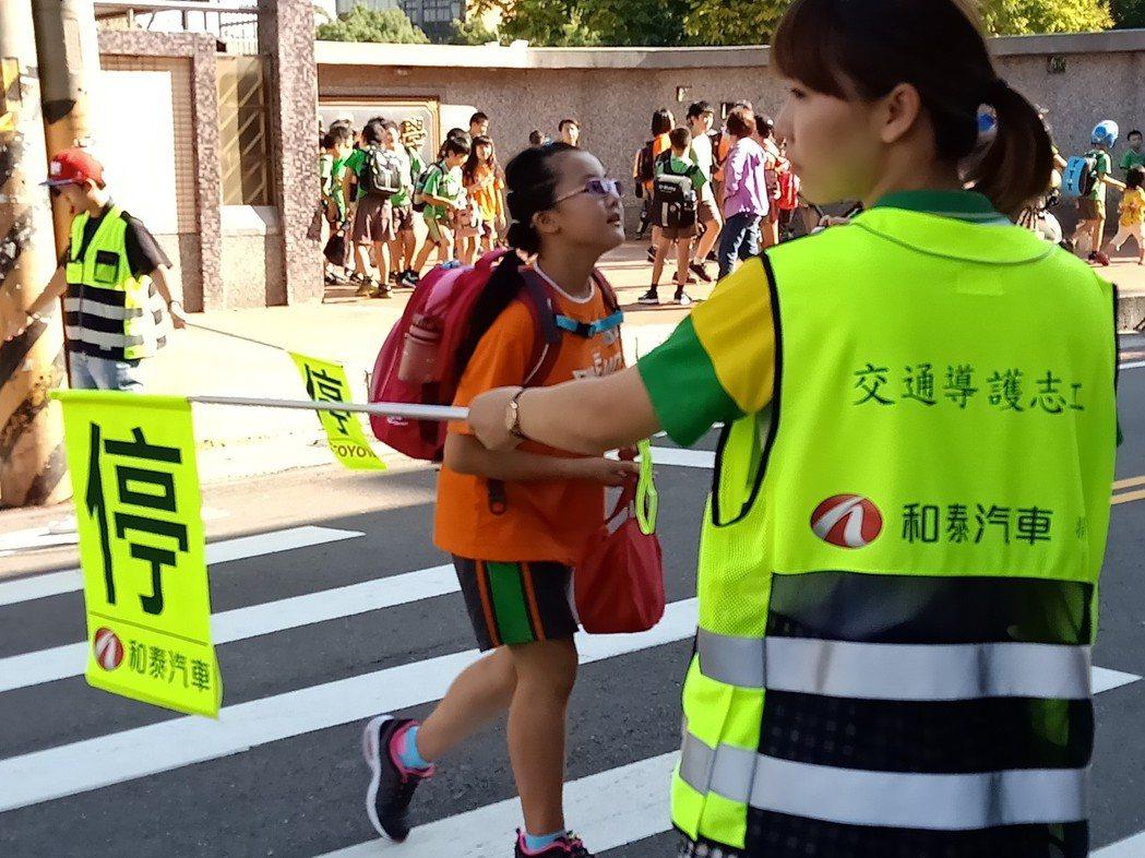 在馬路口第一線保護學童安全的交通導護志工。 圖/和泰汽車提供