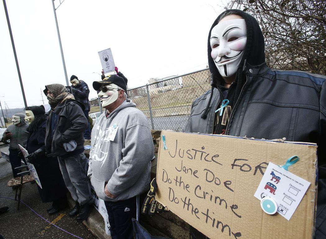 斯托本維爾市兩名高中男生被指控性侵後,數位民眾戴面具、以標語在少年法庭外示威。 圖/路透社