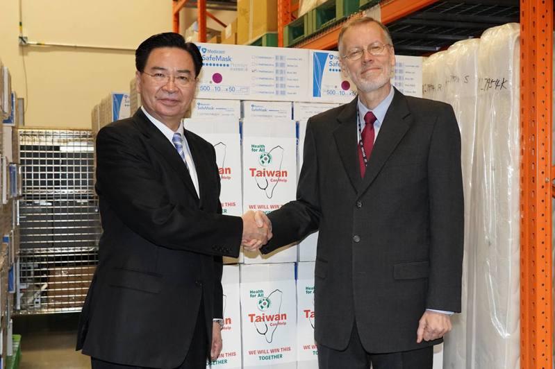 外交部今天表示,可供15萬件防護衣的原料已經運抵台灣,圖為外交部長吳釗燮(左)和美國在台協會處長酈英傑在台灣捐給美國的口罩前拍照。圖/取自AIT臉書
