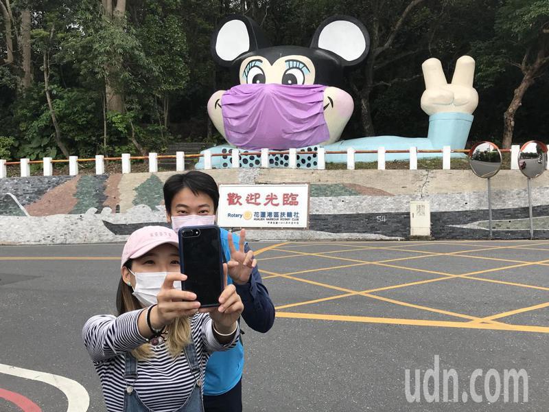 花蓮市公所發揮創意為美崙山米老鼠戴口罩,市長魏嘉賢(右)今天下午到場看米老鼠換裝,與打卡遊客合影。記者王燕華/攝影