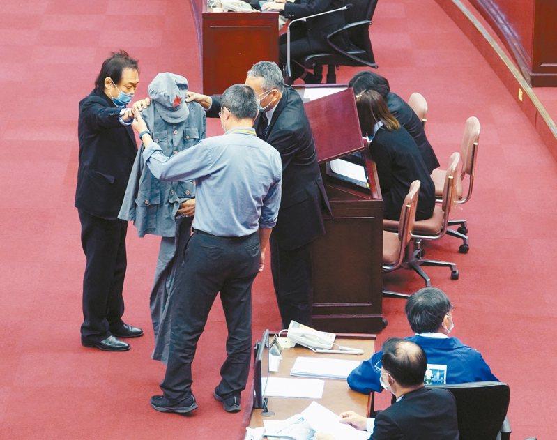 市議員王世堅(左)送柯文哲一件毛裝諷刺他「一分抗疫、兩分市政、七分發展」,由幕僚收下。 記者邱德祥/攝影