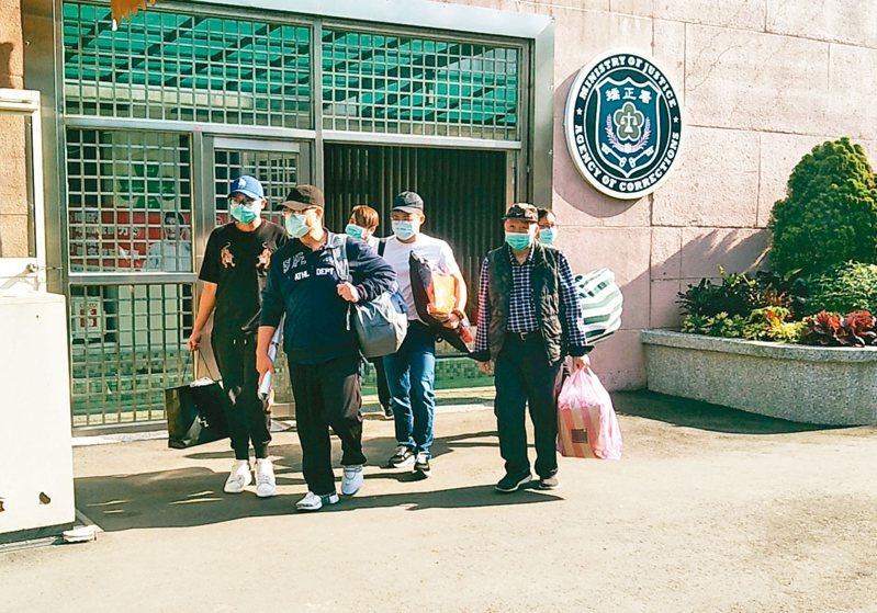 行政院前秘書長林益世(前戴黑帽者)因財產來源不明罪判刑兩年,服刑一年七月後獲假釋,昨天下午步出八德外役監。 記者曾增勳/攝影