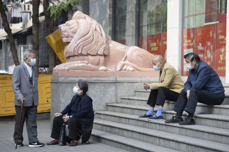 武漢為期8天的篩查,發現當中182人是無症狀感染者,占比約萬分之6.6。圖為武漢市幾位民眾在一家銀行外等候。美聯社