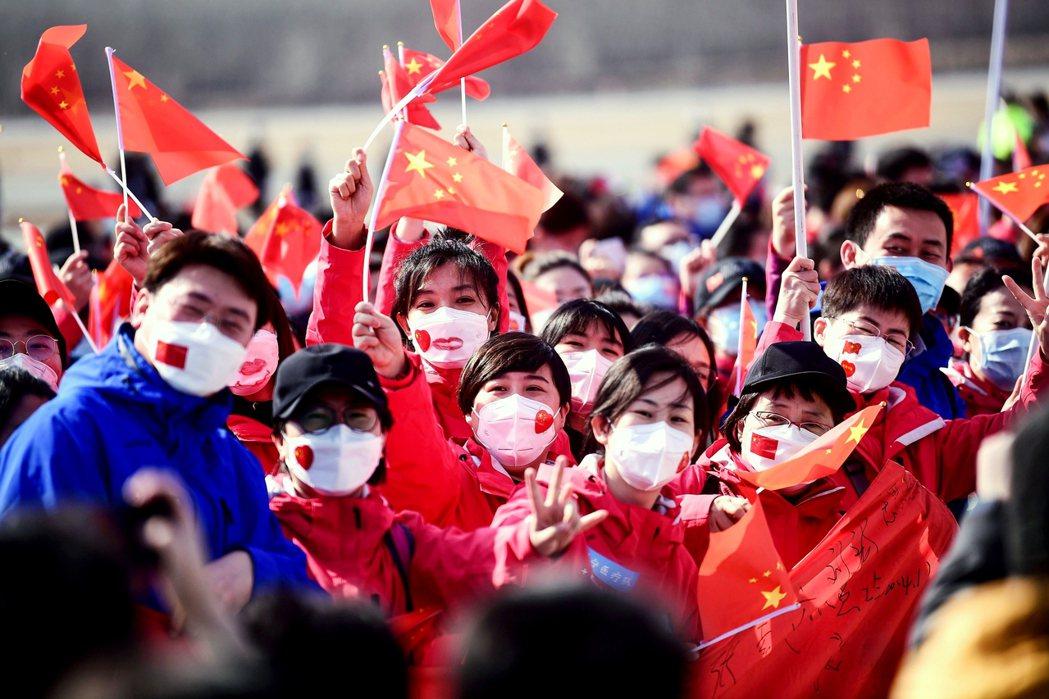 圖為4月1日中國遼寧,民眾揮舞國旗歡迎醫療團隊從武漢返鄉。 圖/法新社