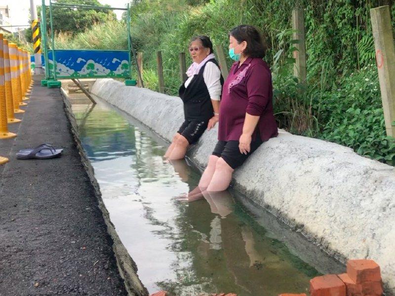 金山區自強路上的臨時停車場,由於有溫泉湧出排水溝成泡腳池,在疫情期間創造新的戶外泡湯點。 圖/紅樹林有線電視提供