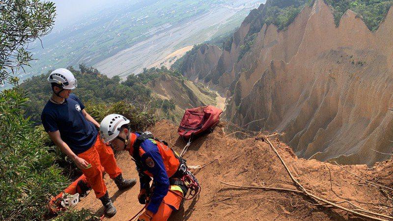 苗栗縣消防局2名特搜隊員以垂降方式到懸崖下方救援,沿途還得躲避落石,其中一人遭落石擊中,嘴唇出現撕裂傷送醫;另一人晚間8點多終於攀回崖頂。圖/苗栗縣消防局提供