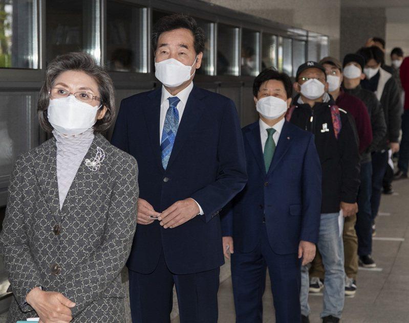 南韓民眾15日排隊等候投票時必須和他人相距約90公分。 新華社
