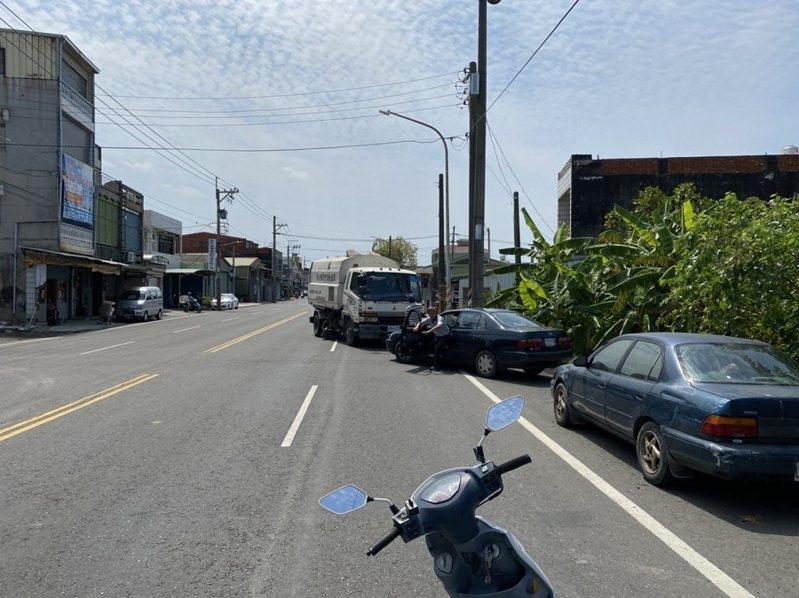 一輛轎車因停車不慎險些掉落路旁農地,熱心司機下車相助。記者徐白櫻/翻攝