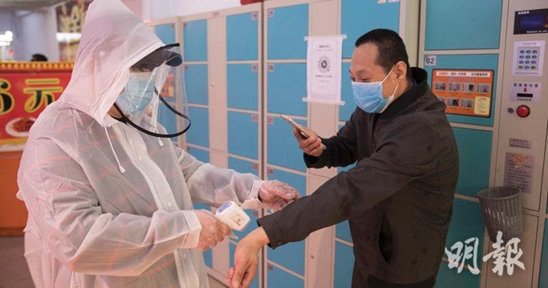 黑龍江省綏芬河市加強防疫,民眾進入超市前雙手需進行消毒。圖/香港明報