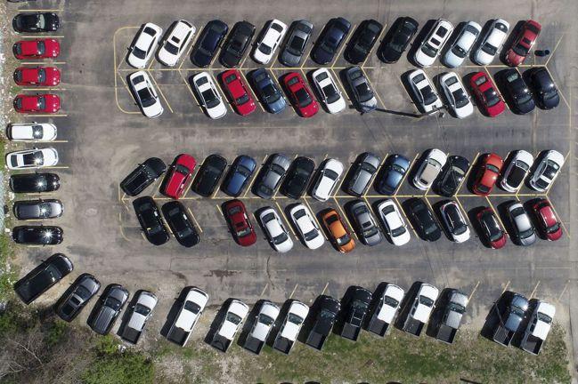 民眾居家避疫,導致美國3月汽車銷售銳減27%,以致一處經銷商停放大量汽車待售。圖...