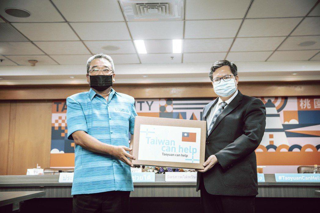 桃園市長鄭文燦(右)遞交防護衣紙箱給泰國貿易經濟辦事處代表通才(左)。 桃園市政...