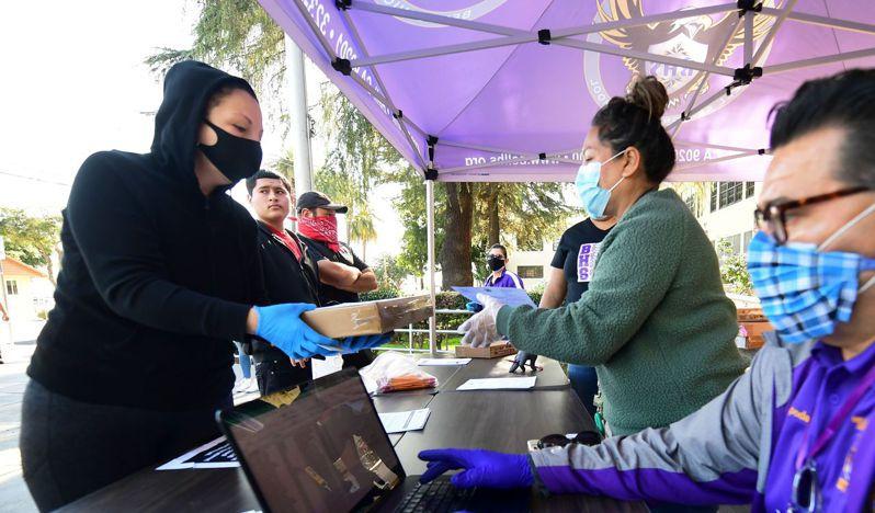 加州洛杉磯郡貝爾市的家長和孩子十五日在貝爾高中領取進行遠距教學所需的筆記型電腦。法新社