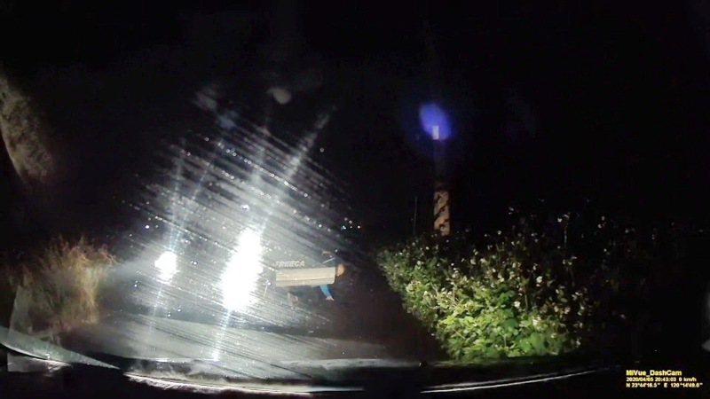 一輛停在路邊打著強燈的車,突然鑽出一人倒地,嚇壞了正要上夜班的民眾。記者蔡維斌/翻攝