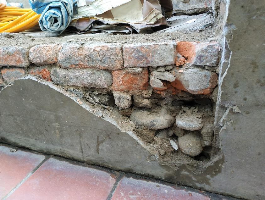 新莊廟街街屋多以鵝卵石鋪底作為地基,再磚砌成牆。 圖/作者自攝
