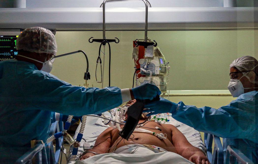 巴西聖保羅一家醫院的醫護人員在加護病房治療新冠肺炎病患。法新社
