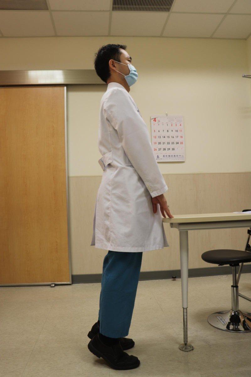 輔大醫院骨科部主治醫師張書豪示範「抬腳跟訓練」,站立並將雙手撐在牢固桌子或椅子上...