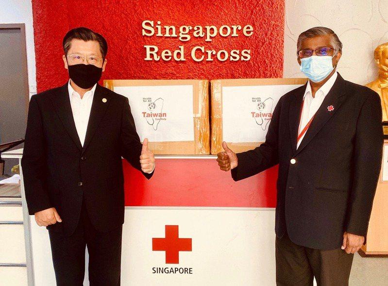 駐星代表梁國新(左)將捐贈的口罩交給新加坡紅十字會執行長Benjamin William(右)。圖/取自駐新加坡台北代表處臉書
