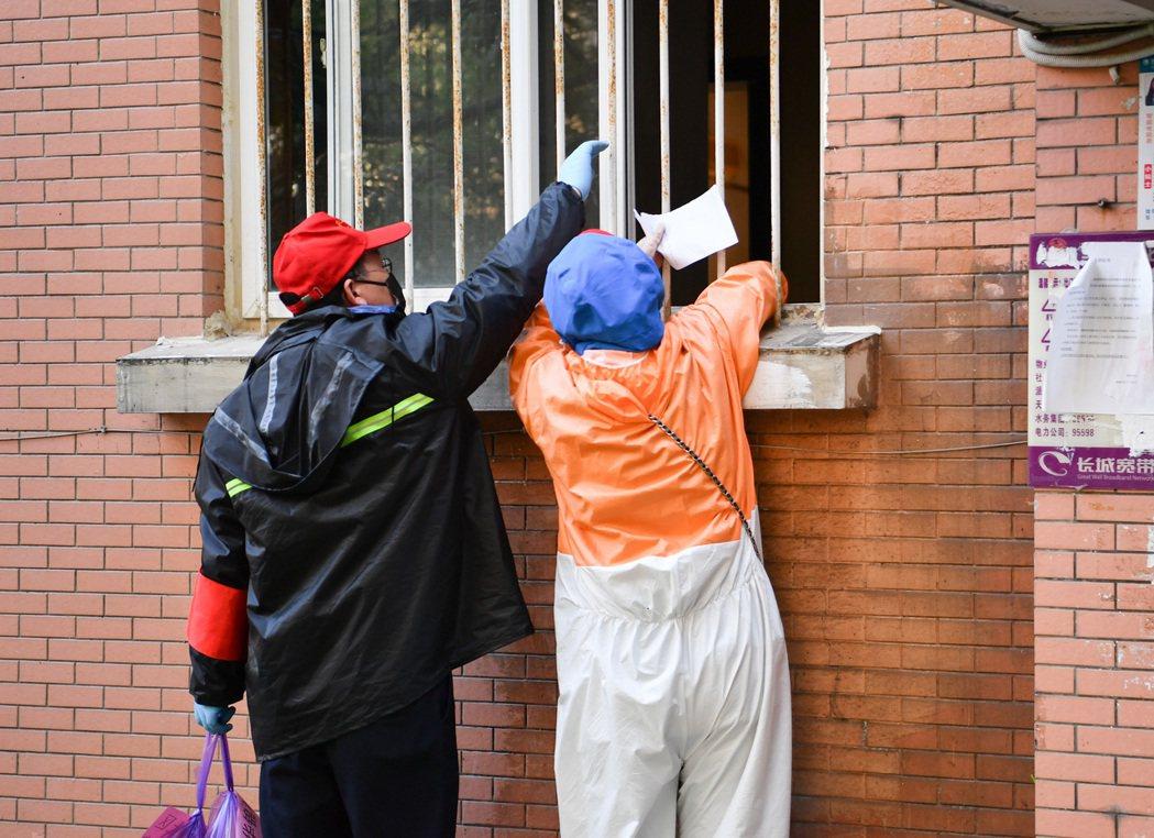 封城期間,志工遞物資給屋內居民。 圖/新華社