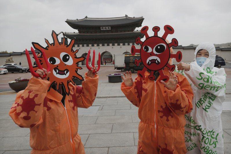 韓國環境衛生協會人員在首爾光化門廣場打扮成病毒模樣。 美聯社
