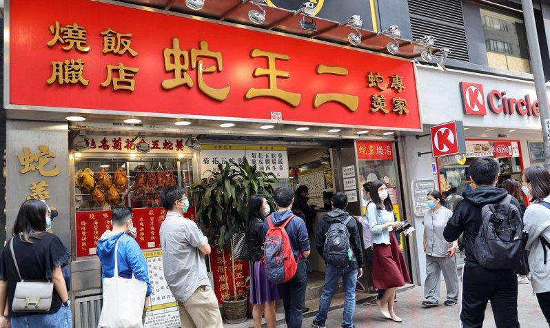 在香港銅鑼灣屹立近40年的「蛇王二」燒臘飯店24日吹熄燈號,23日店外大排長龍,許多熟客紛紛趕來與老店道別。 中新社
