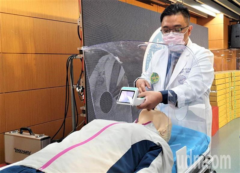 恆春旅遊醫院麻醉科主任邱豑慶今天介紹並示範輕便防飛沬防疫箱使用方法,他說,3片透明塑膠片看似簡單,光是造型設計就傷透腦筋,最終希望變成拋棄式。記者潘欣中/攝影