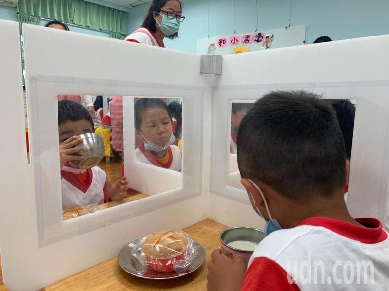 新冠肺炎防疫,宜蘭縣羅東鎮幼兒園幼童吃午餐時,要維持足夠的社交距離,園方因此在餐桌上設隔板,沒想到這反引起幼童好奇,常常探頭看看鄰童在做什麼,園方為此利用翻翻書的原理,製作有透明板視窗版的隔板,讓幼童吃飯也可以對看,因防疫產生創意。 圖/羅東鎮公所提供