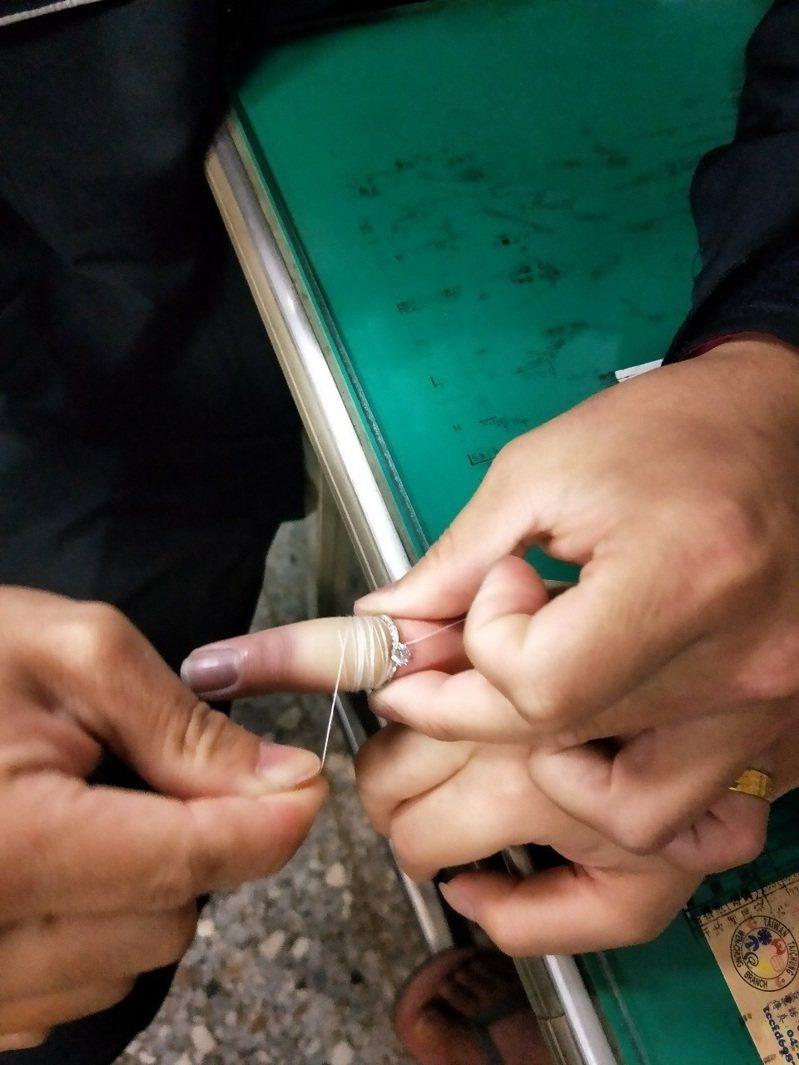 呂姓女子婚戒卡手指已2天,手指整個腫脹,到中市消防局文昌分隊求助,呂女表示結婚紀念戒指很重要,不希望被破壞,打火兄弟用在網路看到的新招,頭一次使用縫紉線來脫戒,順利取下呂女的婚戒。圖/台中市消防局文昌分隊提供