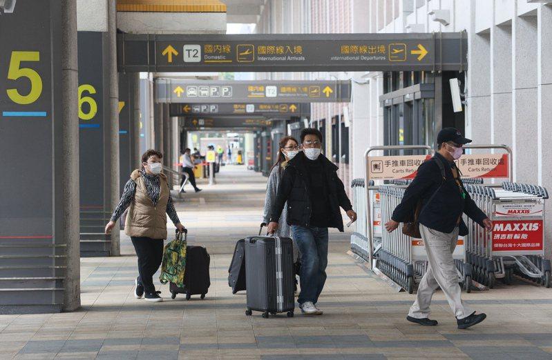 新冠肺炎疫情持續延燒,松山機場不少旅客和民眾戴著口罩進出機場。 中央社