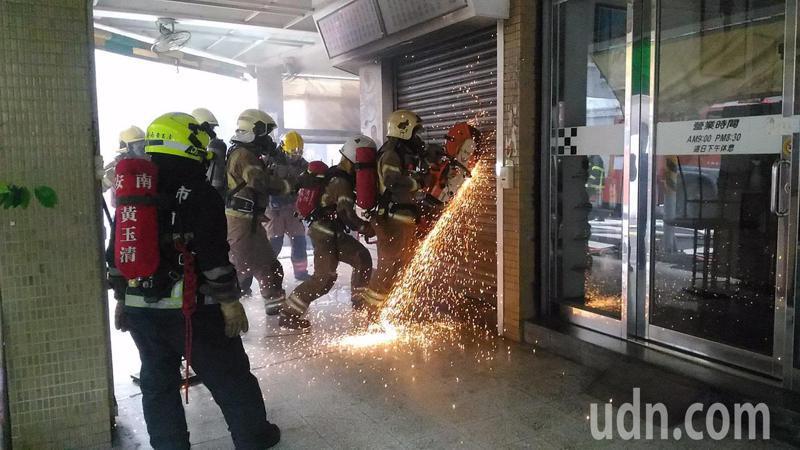 消防人員以破壞器材切開冰店鐵捲門,入內滅火。記者黃宣翰/攝影
