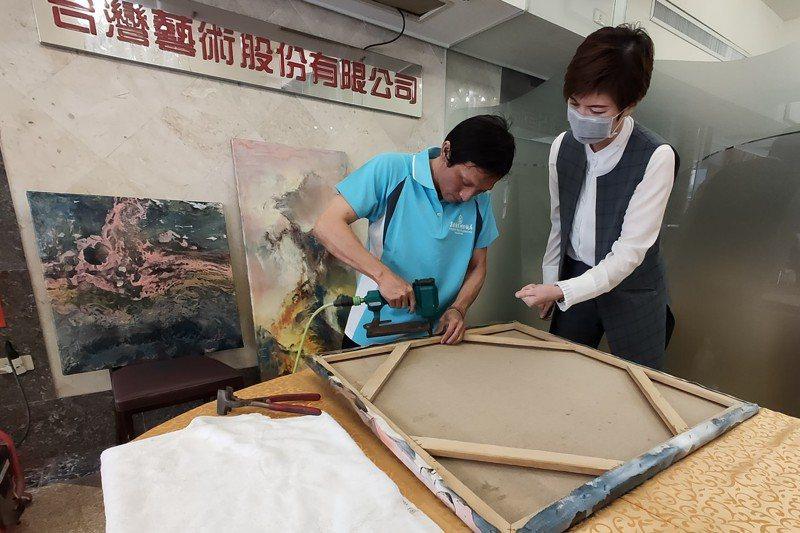 擔任電工近20年的柯志明(左),接受特訓一個多月後,搖身一變成為「油畫裱框師」,他笑說多學東西比較不怕沒工作。 記者蔡容喬/攝影