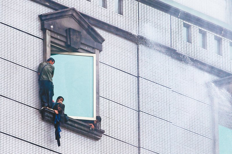 台北市林森北路錢櫃KTV昨天發生大火,受困民眾爬到窗邊等待救援時,消防隊員持續灑水為他們降溫。 記者葉信菉/攝影