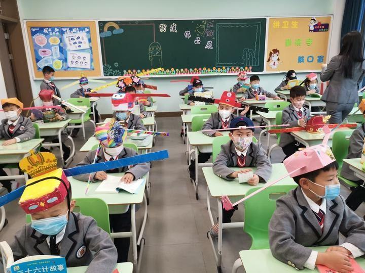 小學生頭戴一米帽保持社交距離。圖片來源/ 騰訊