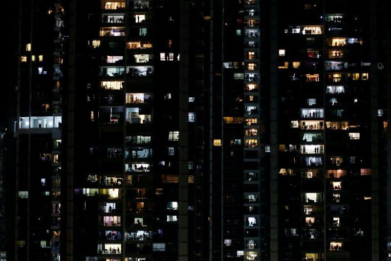 4月25日,新加坡公民在自宅陽台為第一線人員及移工加油打氣。 圖/路透社