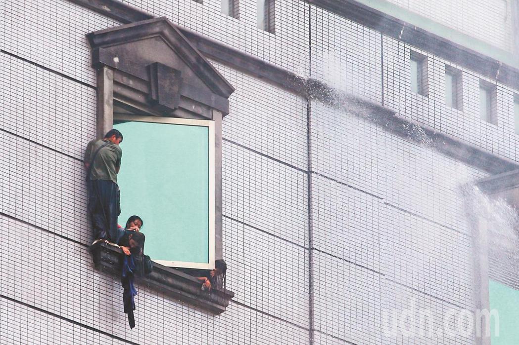 台北市林森北路錢櫃KTV昨天發生大火,受困民眾爬到窗邊等待救援時,消防隊員持續灑...