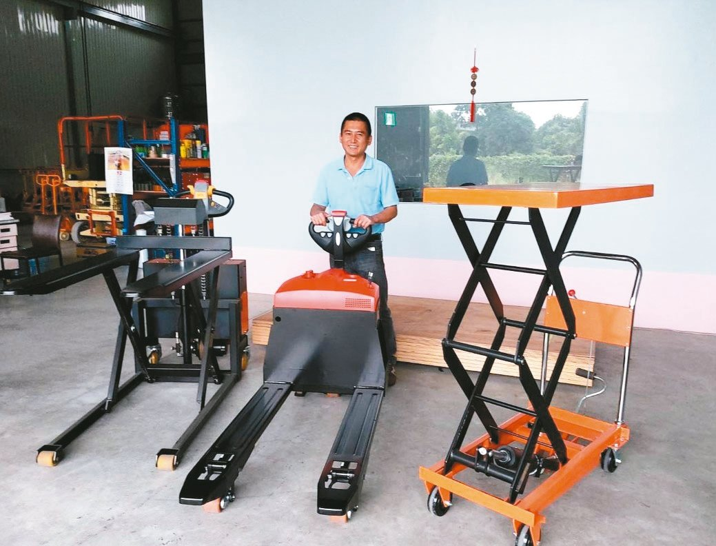 大器機械業務經理許瑞宏展示近期熱銷的「牽引式電動拖板車」、「全電動高揚程拖板車」...