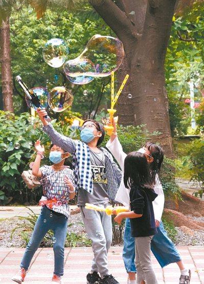 新冠肺炎全球肆虐下,台灣昨天再傳出零確診好消息,一群小朋友在大人陪同下到戶外戴著口罩玩泡泡,疫情警報何時遠離讓生活恢復正常是全民的企盼。 記者潘俊宏/攝影