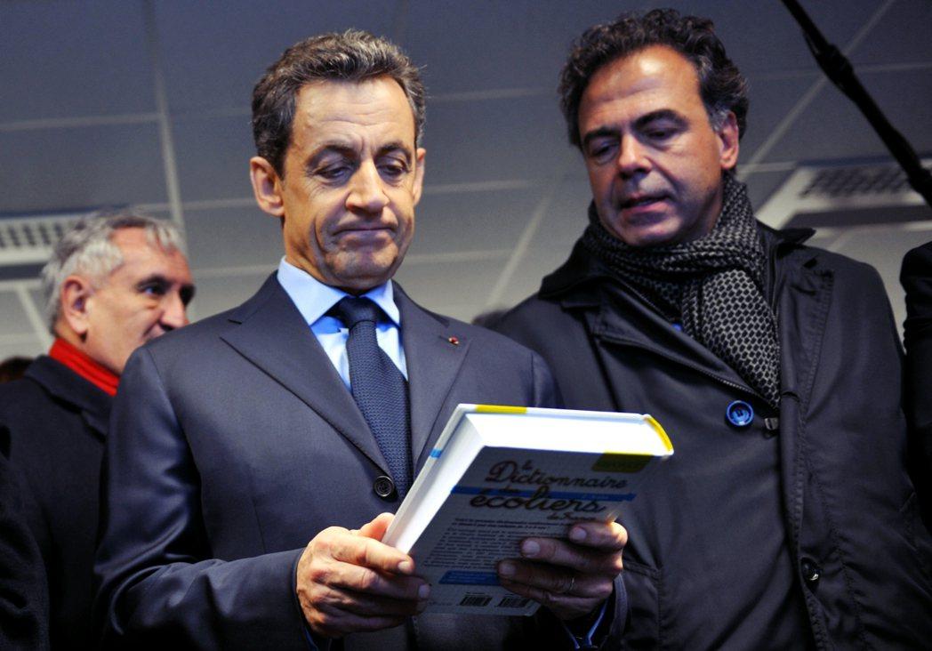 圖為拿著一本法語字典的法國前總統薩科奇(Nicolas Sarkozy)。 圖/...