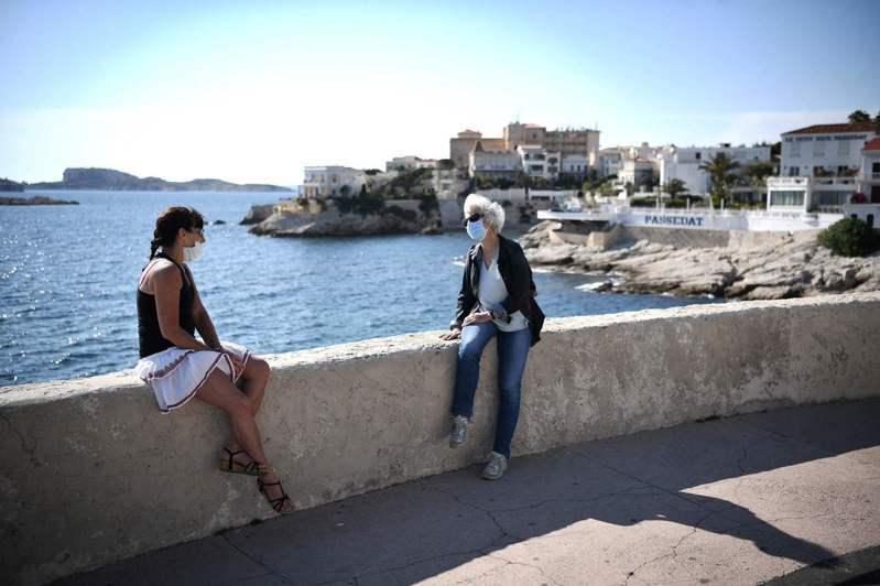 法國預定五月十一日起逐步解封。圖為南部大城馬賽的民眾廿五日在海岸邊聊天。(法新社)