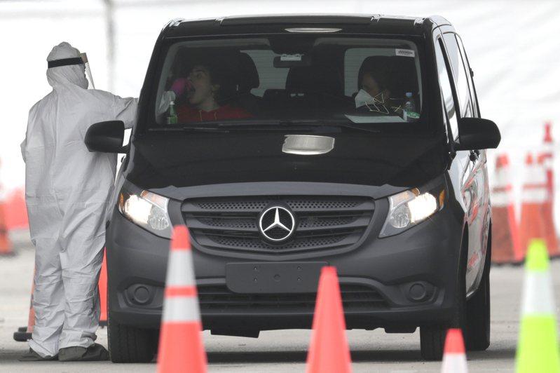 美國佛州的「富人天堂」費雪島能買到數千套新冠病毒檢測套組,佛州其他地區檢測率卻僅1%。圖為佛州一名醫護人員為一個開車民眾進行檢測。