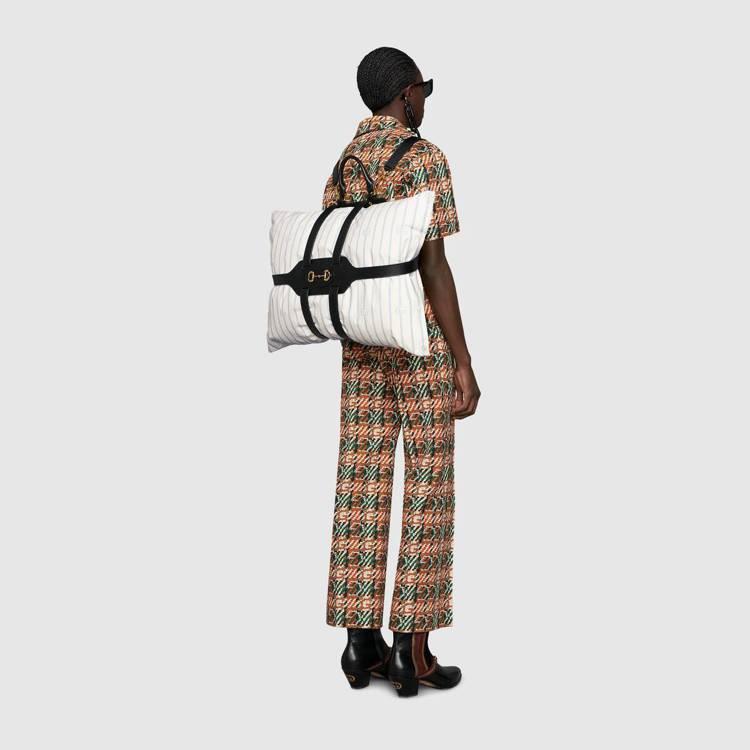 GUCCI推出一個像是枕頭背帶的物件,這個可以背又配有一個提把的皮革物件正中間有...