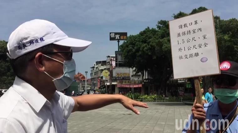 高雄市觀光局長邱俊龍(左)請在風景區協助防疫的人員要注意遊客有沒有保持社交距離。...