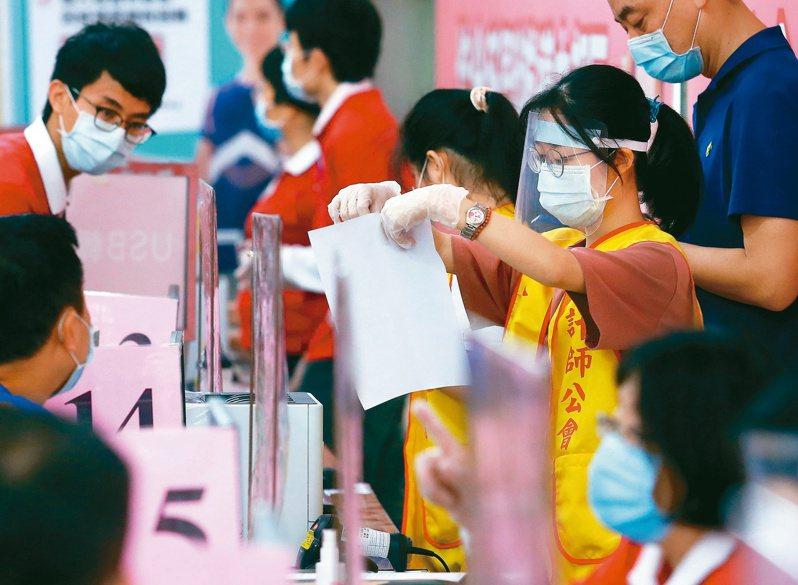 台北國稅局昨湧現臨櫃報稅人潮,櫃檯安裝透明隔板,工作人員更戴上護目鏡、口罩、手套等裝備,一邊防疫,一邊協助民眾報稅。記者杜建重/攝影