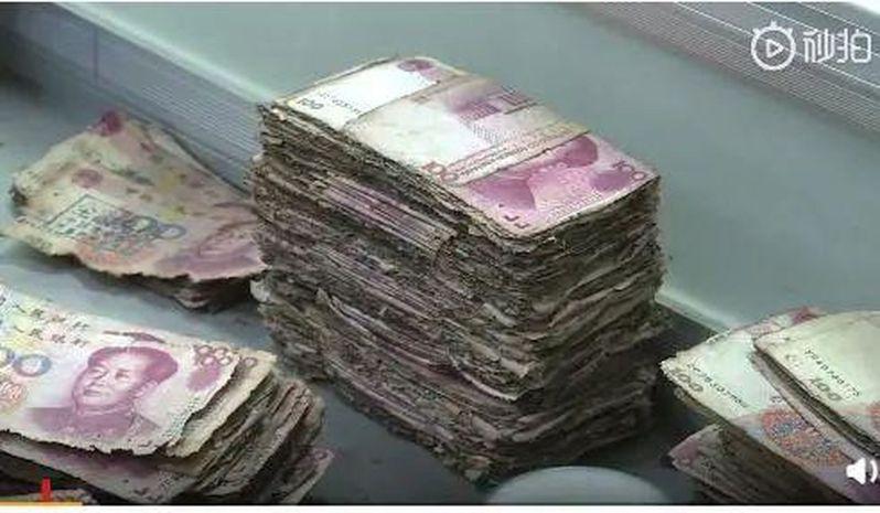 大陸一對夫妻將200萬元人民幣的紙鈔埋入土裡,但部分紙鈔已發霉,無法至銀行換新鈔,令其損失將近人民幣50萬元。圖/影片截圖