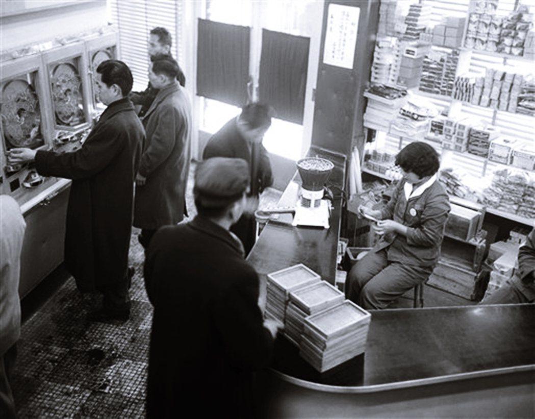 1955年日本東京的某間柏青哥店,右方櫃台後面的兌換獎品已經開始提供香菸。 圖/...