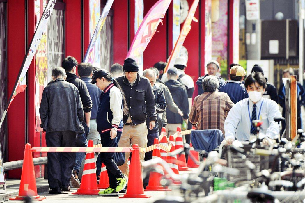 圖為4月日本柏青哥店外大排人龍的隊伍。政府多次點名柏青哥業者,要求自肅閉店,但效...