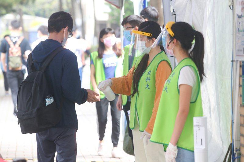 統測是新冠肺炎爆發後第一場高規格防疫的升學考試,工作人員身著全套防護裝備,站在入口處幫考生量測體溫、噴酒精消毒。記者葉信菉/攝影