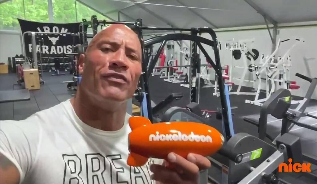 巨石強森在自家健身房領獎。圖/摘自Youtube