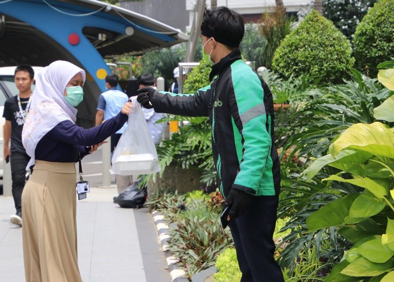 印尼全能到府服務業者防疫用心,許多騎士載客和遞送餐飲都戴上口罩。