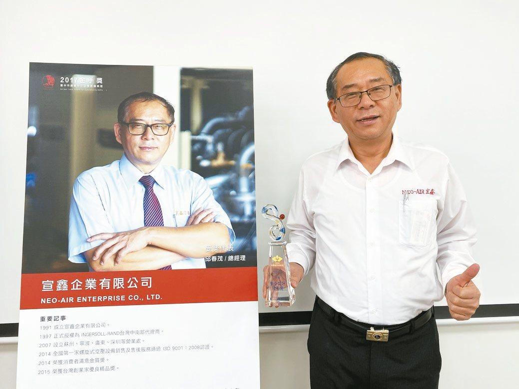 宣鑫公司總經理邱春茂展示該公司獲頒的台灣優良商標獎獎座。 黃奇鐘/攝影
